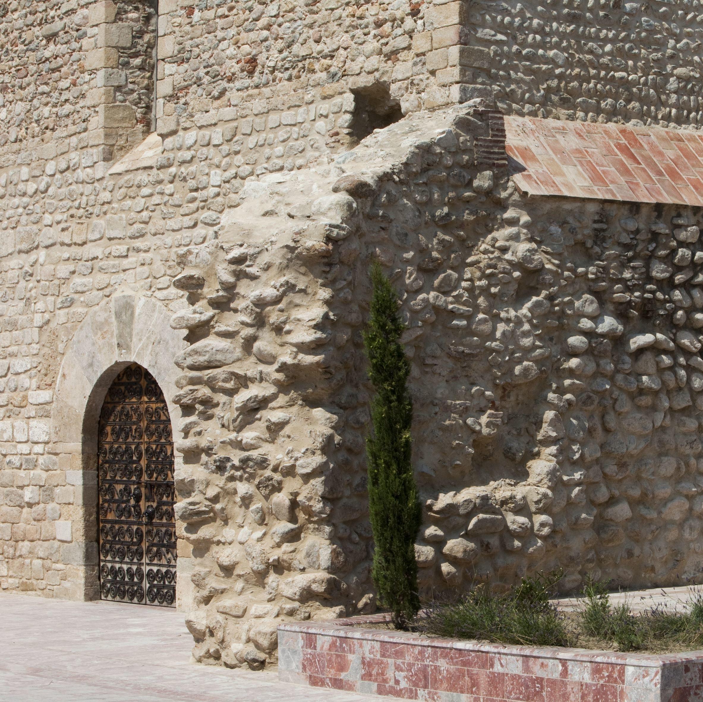 Mur épais adossé à l'église, vestige de l'ancien Palais du village fortifié